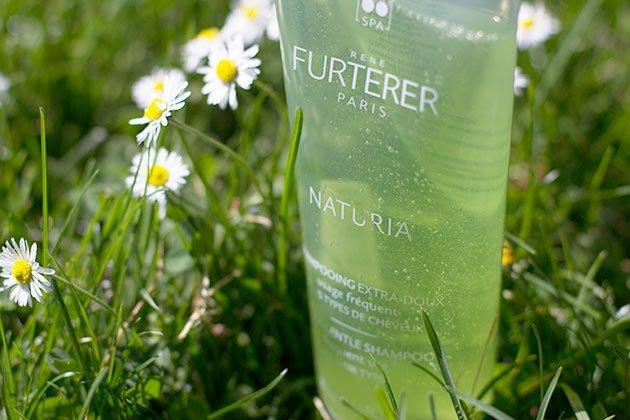 Shampoing Naturia de Furterer dans l'herbe et pâquerettes