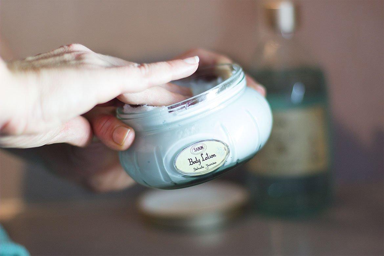 Main qui plonge dans un pot de Crème corporelle Jasmin Sabon