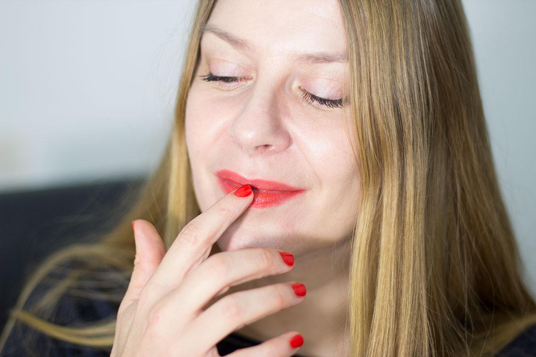 femme qui estome rouge à lèvres avec les doigts