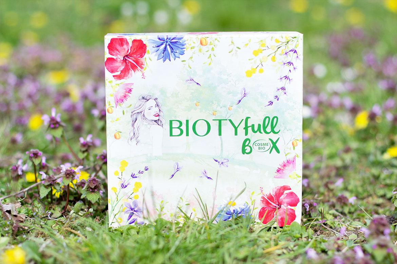 boîte de Biotyfull Box Avril Cosmebio parmi les fleurs