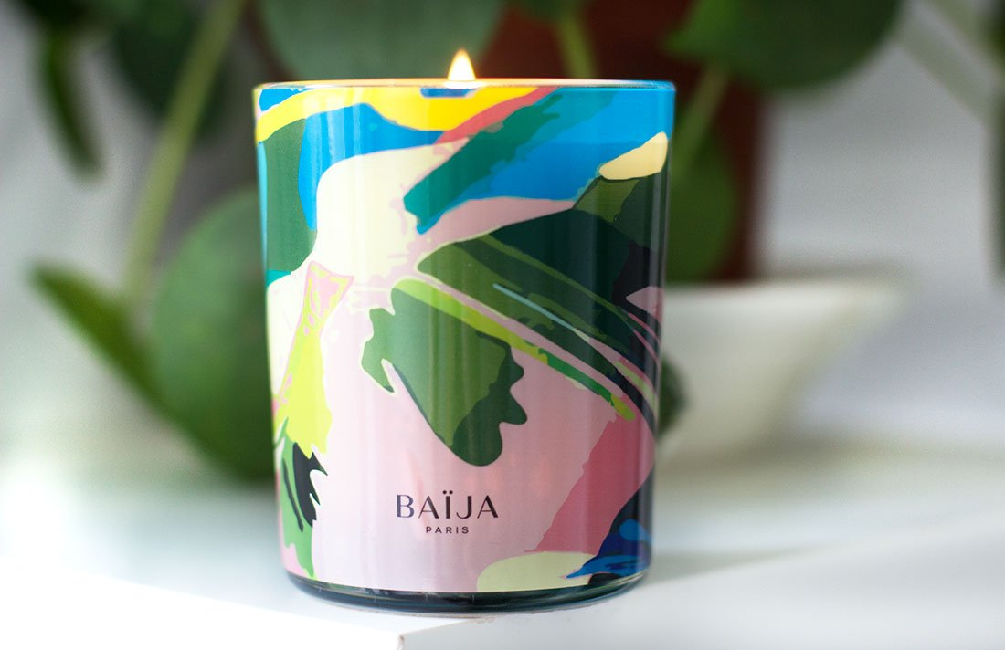 bougie parfumée Baïja posée devant plante