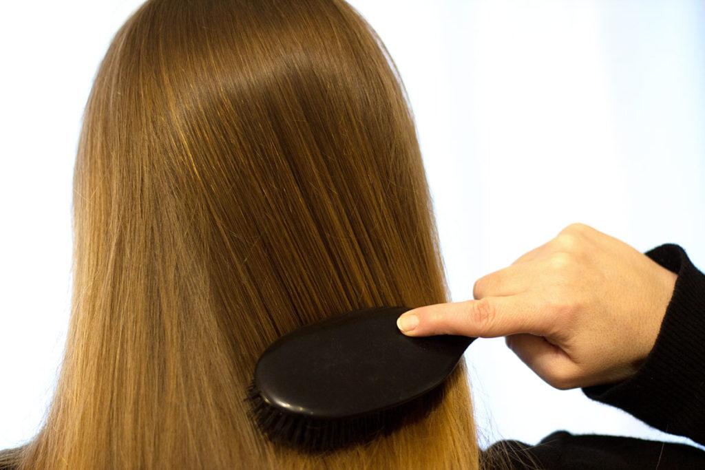 femme qui se brosse les cheveux avec brosse Mason Pearson